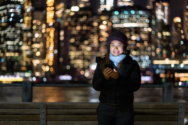冬のアジアの女性は、ニューヨークの街並みのボケぼやけた写真に笑顔アクションでスマートな携帯電話を使用してスーツします。 Premium写真
