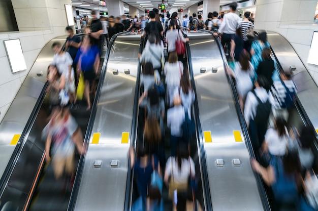 歩行者の群衆地下鉄交通ハブ、香港、中央地区での勤務時間前のラッシュアワーの朝にエスカレーターで認識できない歩行 Premium写真