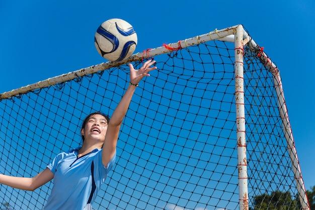 若いアジアの女の子のゴールキーパーボールをキャッチ Premium写真