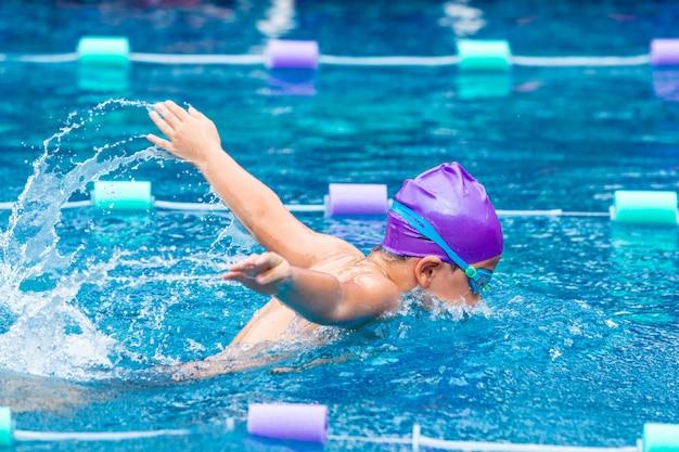 彼の蝶ストロークを練習している若い男の子の水泳 Premium写真