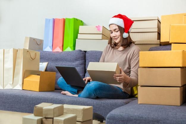彼女のオンラインビジネスに取り組んでいる、クリスマスの帽子をかぶっている若いアジア女性オンライン売り手起業家 Premium写真