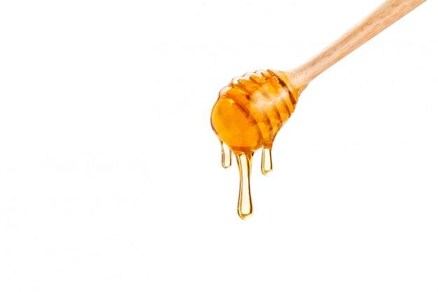 コピースペースと白い背景の上の木製蜂蜜ディッパーから滴り落ちる蜂蜜 Premium写真