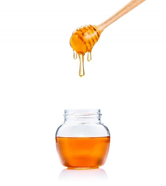 ガラス瓶と白い背景の上のすべての白い背景の上に滴り落ちる蜂蜜と木の蜂蜜ディッパー Premium写真