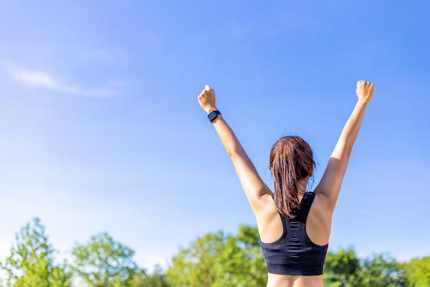 ぼやけた木と澄んだ青い空と屋外のフィールドで楽しく彼女の腕を伸ばして女性の背面図 Premium写真