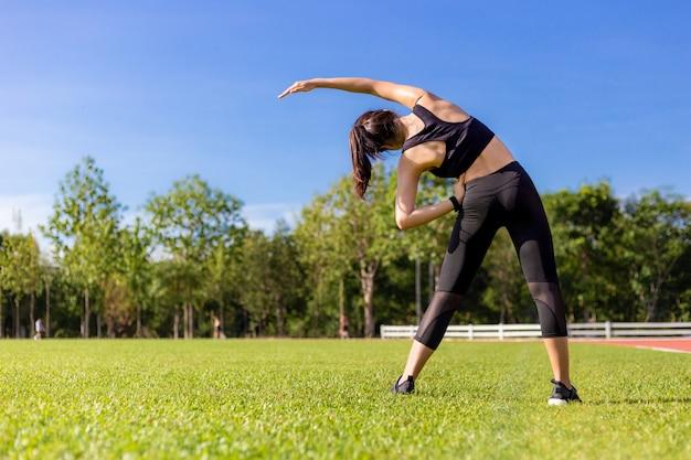 ランニングトラックの芝生のフィールドで彼女の朝の運動中にストレッチ美しい若いアジア女性 Premium写真