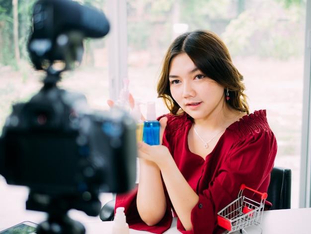 よりきれいな女性が彼女の化粧品ブランドをレビューするインターネットをオンラインで使う Premium写真