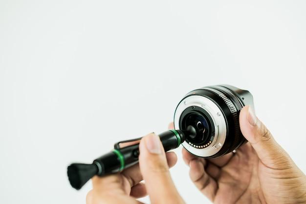 カメラのレンズのクリーニング方法は、白い背景の上の人間の写真でフォーカスを閉じる Premium写真