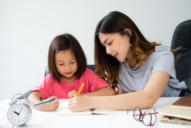 若い女性が自宅で彼女の子供に宿題を教える Premium写真