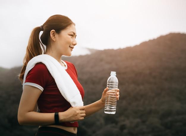 美しいアジアの女性は外で運動し、水を飲む Premium写真