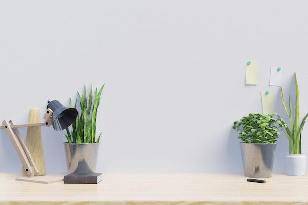 植物のある創造的な机のある現代の職場には白い壁があります Premium写真