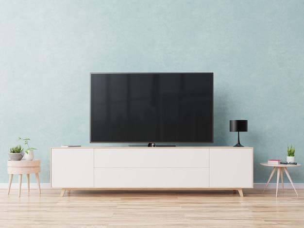 青い壁の背景にモダンなリビングルームのキャビネットのテレビ。 Premium写真