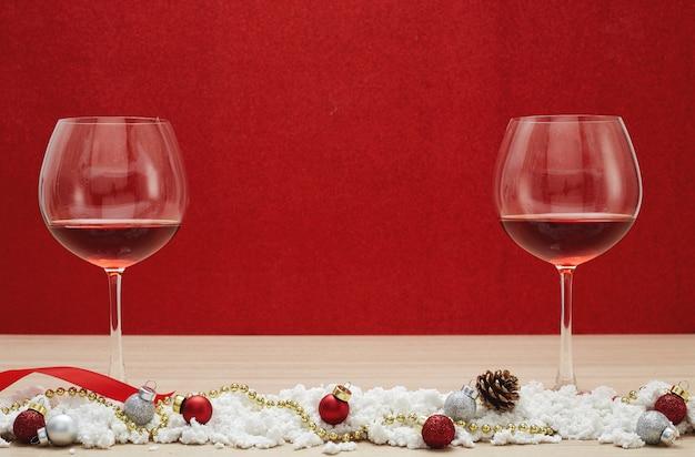 赤ワイングラスと雪のクリスマスボール Premium写真