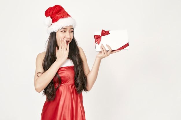 Женщина в шляпе санта держит подарки Premium Фотографии