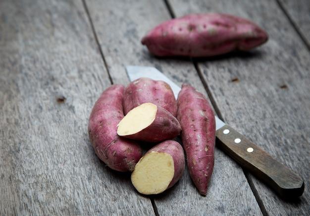 木の背景に生のサツマイモ Premium写真