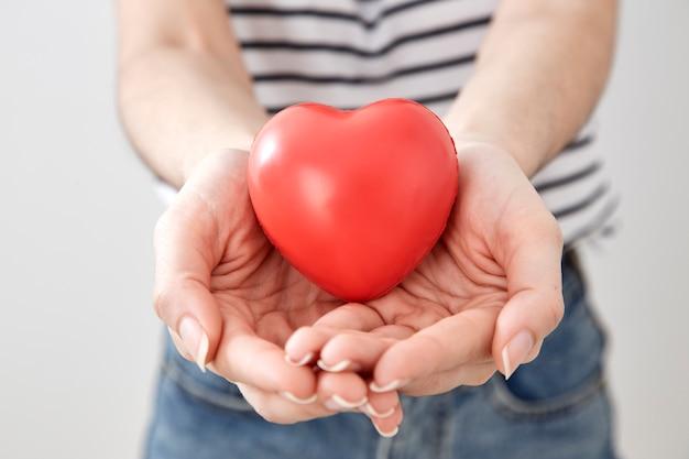 赤い心を示す若い女性の手 Premium写真