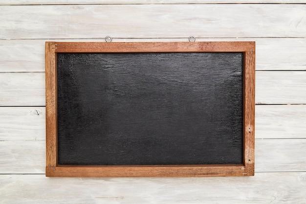 木製の壁に木製のフレームで黒板 Premium写真