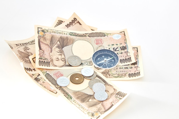 白い背景に日本の円の紙幣と円のコインとコンパス Premium写真
