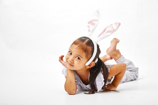 ピンクの耳のウサギを持つ少女 Premium写真