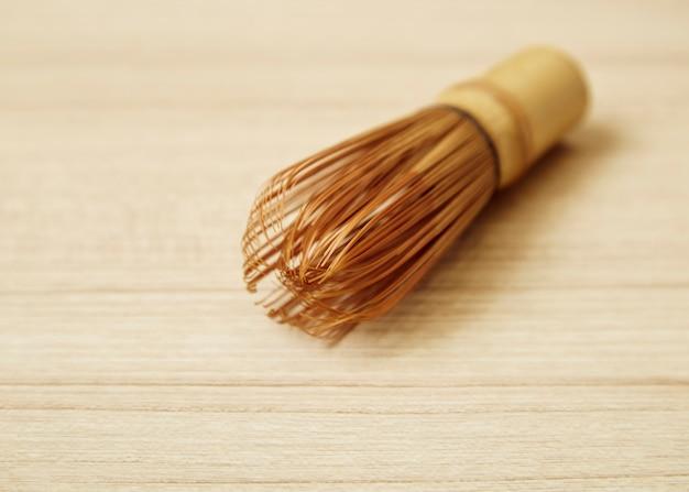 木製のテーブルに抹茶の竹茶泡立て器 Premium写真