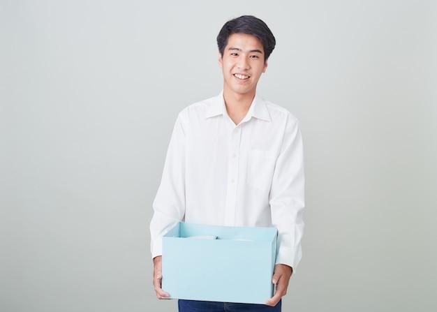 Молодой азиатский бизнесмен держа коробку Premium Фотографии