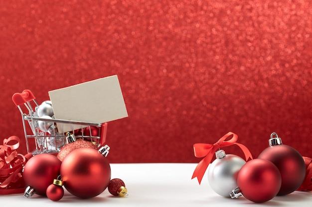 赤い背景の上のクリスマスの飾りのショッピングカート Premium写真