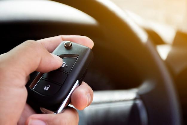 ドライバーの手は、キーレスのリモートカーに押し付けられます。 Premium写真