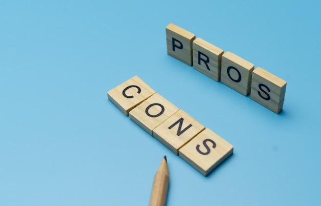 鉛筆で指している青い表面の木製ブロックの「長所と短所」の単語 Premium写真