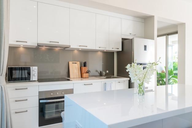 プールヴィラのリビングルームの豪華なインテリアデザイン。高く上げられた天井とダイニングテーブルのあるキッチンエリアのある広々とした明るい Premium写真