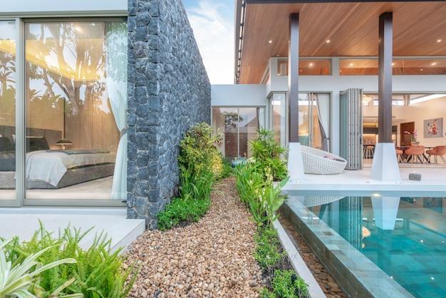 緑の庭園と寝室のあるトロピカルプールヴィラを示す家または家の外観デザイン Premium写真