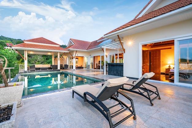 太陽のベッド付きのトロピカルプールヴィラを示す家または家の外観デザイン Premium写真
