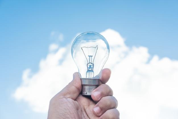 電球と青い空を持っている手 Premium写真