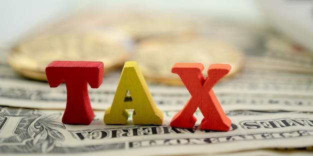 Деревянное налоговое слово на банкноте и золотой монете. концепция уплаты налогов, льгот или обязательных финансовых сборов. Premium Фотографии