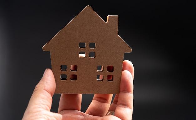 Рука человек, держащий деревянный модельный дом. концепция строительства и ремонта дома. Premium Фотографии