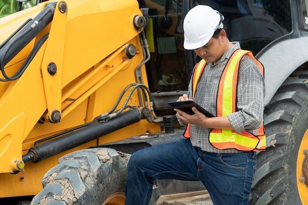 Инжиниринг в белом защитном шлеме перед экскаватором Premium Фотографии