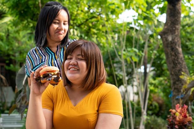 太りすぎの女性は車椅子でハンバーガーを食べています。 Premium写真