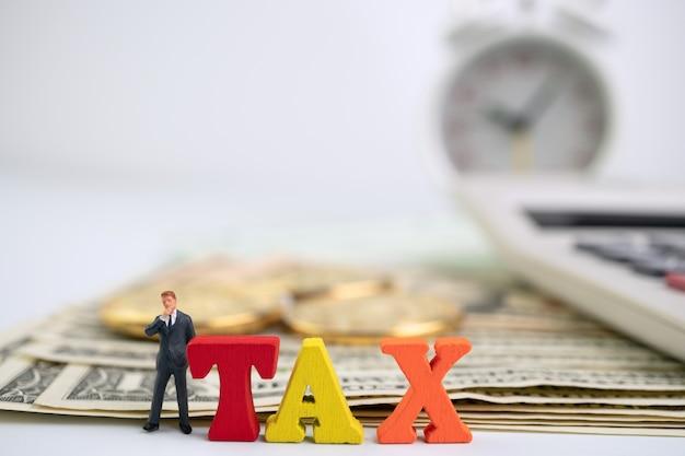 Фигура бизнесмена, стоящего возле дерева налоговое слово на банкноте и золотой монете и калькуляторе Premium Фотографии