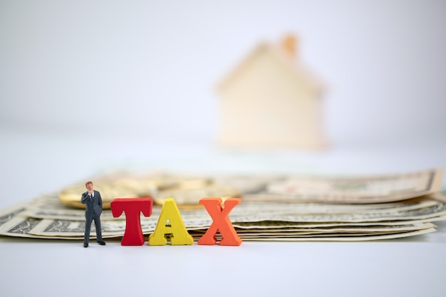 Фигура бизнесмена, стоящего возле дерева налоговое слово на банкноте и золотой монете и деревянном доме Premium Фотографии