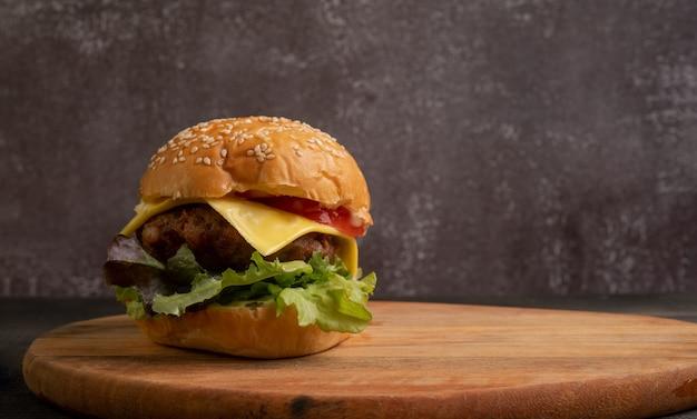 まな板の上の新鮮な野菜と新鮮なおいしい自家製ハンバーガー。 Premium写真