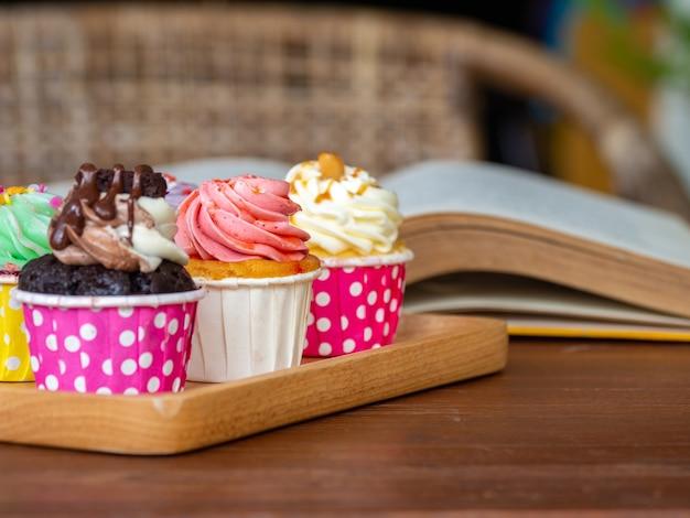 Красочный из домашнего кекса на деревянный поднос и открыть книгу на деревянный стол. Premium Фотографии