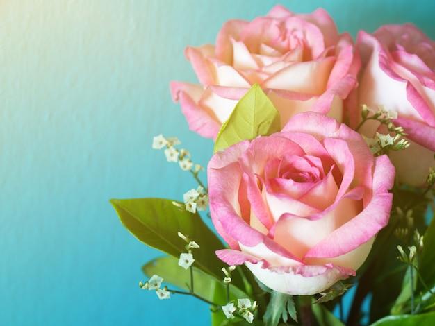 Розовые розы на синем фоне и утреннее солнце Premium Фотографии