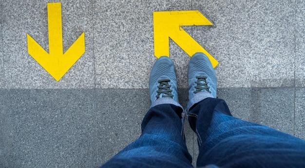 地下鉄のプラットフォームで矢印記号の上に立っている人の足の上から見る。 Premium写真