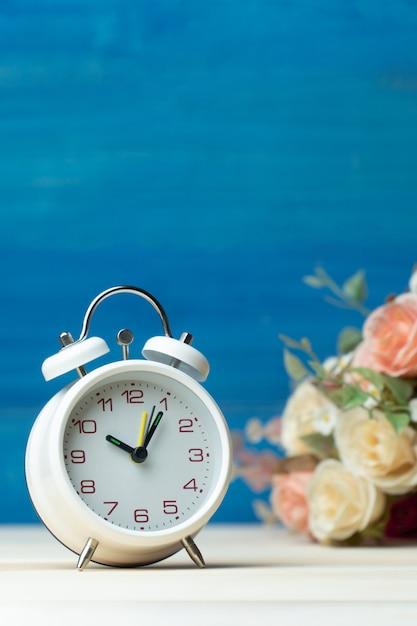Белый будильник и цветы розовые и красные розы на деревянный стол и синий фон Premium Фотографии