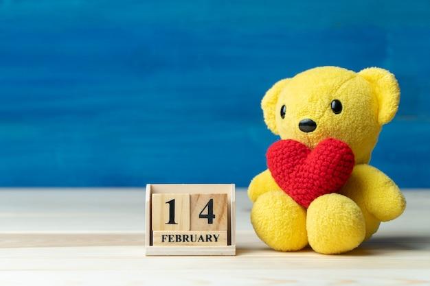 バレンタインデーに設定された木製のブロックカレンダーの横にある黄色のテディベアに手を作る赤い糸ハート Premium写真
