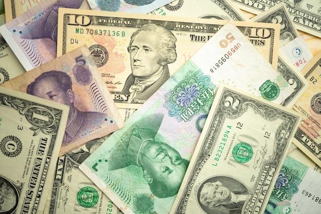 Стек доллара сша и банкноты китайского юаня на столе Premium Фотографии