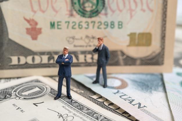 米ドルと元紙幣の上に立って、考えて図実業家。 Premium写真