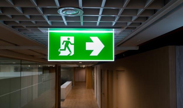 緑の火災避難標識は、オフィスの天井に掛かっています。 Premium写真