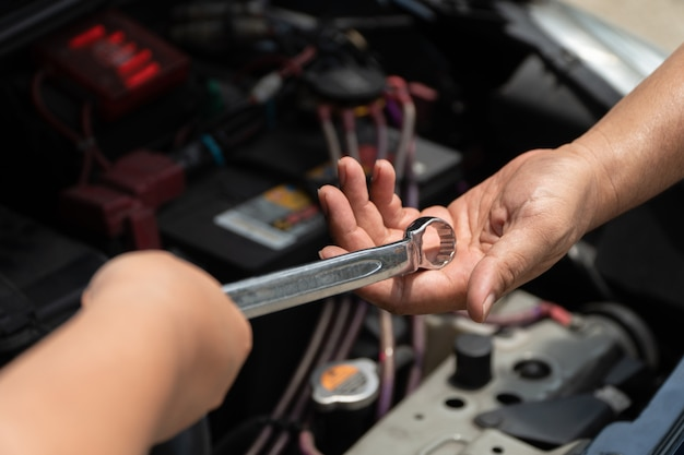 車のエンジン修理工サービスの技術者の頭が同僚にレンチを提供 Premium写真