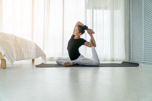 Среднего возраста женщины занимаются йогой в спальне утром, упражнения и отдых утром. Premium Фотографии