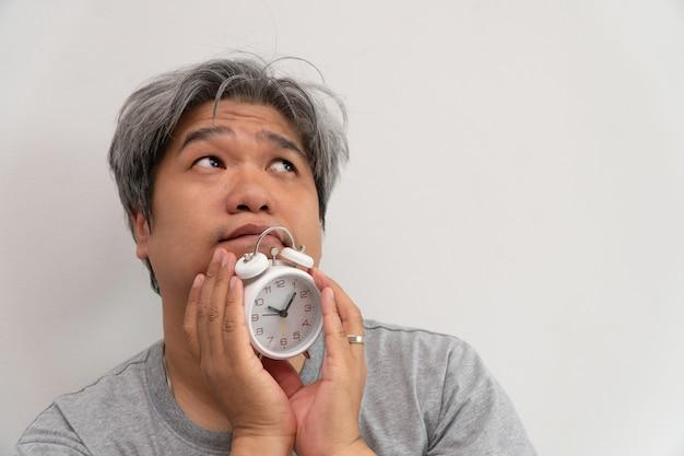 アジアの中年男性が白い目覚まし時計を持っていると、彼の顔は退屈と気分が悪くなり、 Premium写真