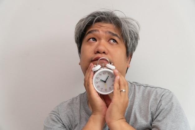 アジアの中年男性が白い目覚まし時計を持っていると、彼の顔は退屈と気分が悪く、彼の問題は睡眠障害です。 Premium写真